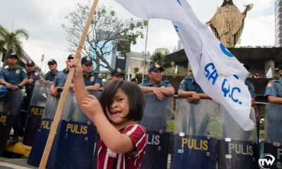 child waving a flag in front of riot police during people power revolution